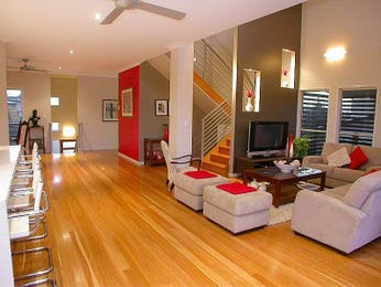 Open plan living room using brown colours with hardwood & staircase - Living Area photo 353677