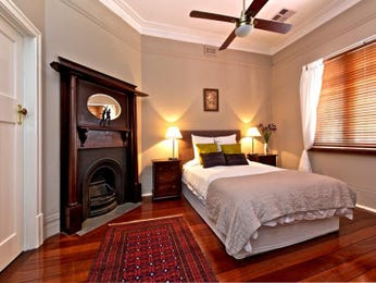 Country bedroom design idea with floorboards & fireplace using brown colours - Bedroom photo 194928