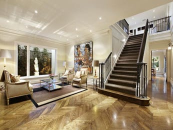 Split-level living room using beige colours with hardwood & staircase - Living Area photo 257417