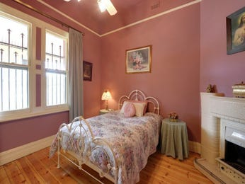 Country bedroom design idea with floorboards & fireplace using pink colours - Bedroom photo 987872