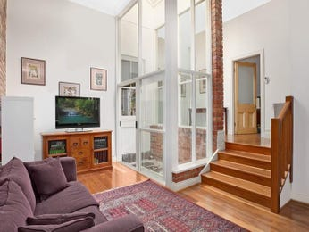 Split-level living room using brown colours with floorboards & staircase - Living Area photo 1342042
