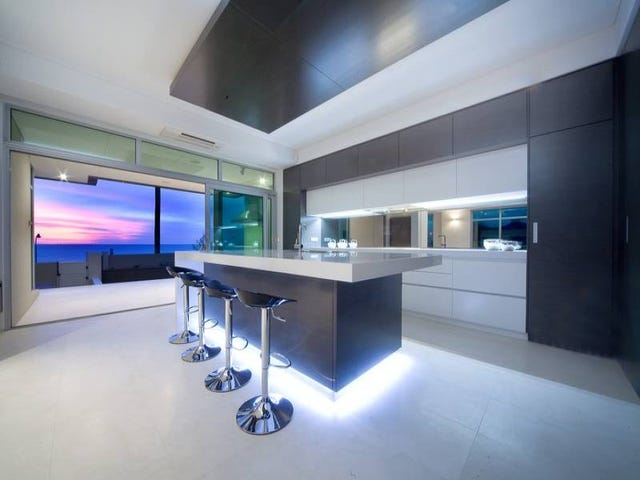 The bench top lighting with sleek lines compliment the twilight view. A perfectly designed sleek and contemporary kitchen designed to take in the wonderful views.
