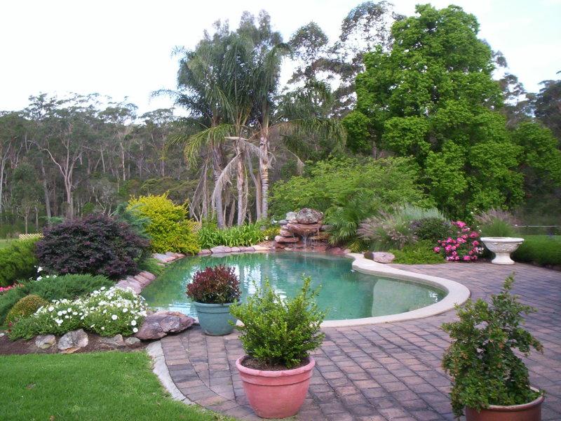 Tropical garden design using brick with fish pond for Garden pond rockery ideas
