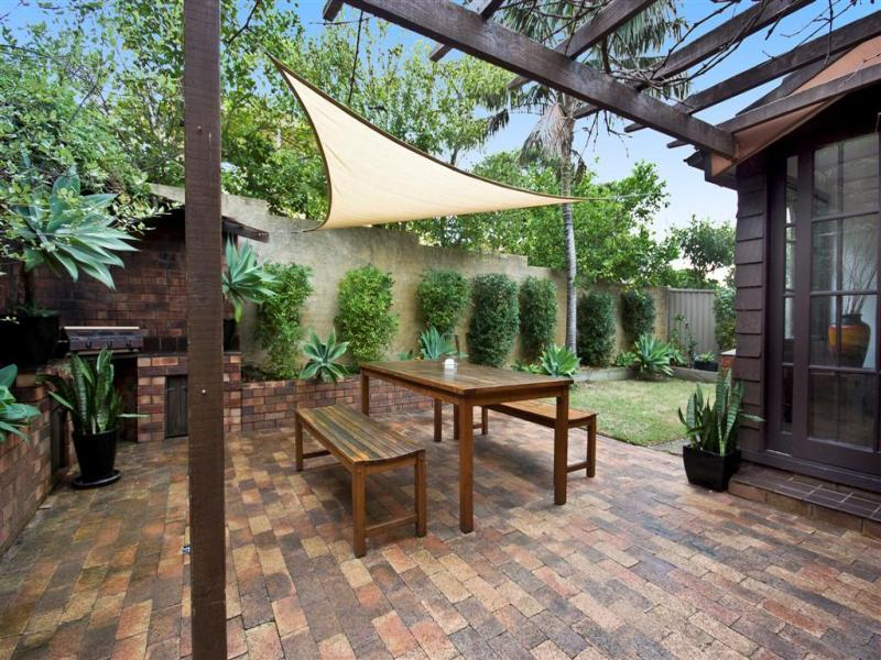 Indoor-outdoor outdoor living design with bbq area & shade ... on Shade Sail Backyard Ideas id=24404